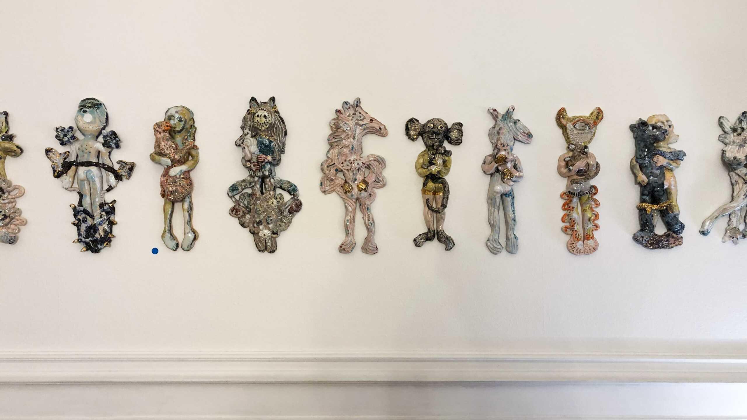 Saraï Delfendahl's amusing ceramic figures dancing on the wall